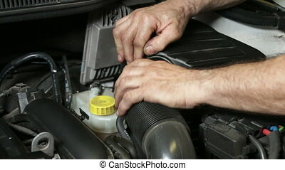 A repairman assembling the air cooling system of the engine. Car reparation and test. Mechanic doing a car review.