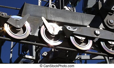 Mechanic moving shiny gear wheels gondola lift closeup