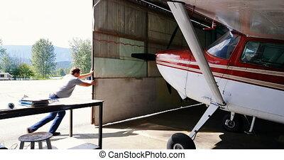 Side view mechanic opening hangar gate 4k