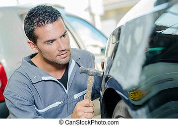 Mechanic panel beating a car