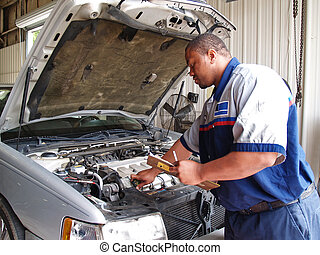 Auto mechanic checking radiator levels while performing a routine service inspection in a service garage.