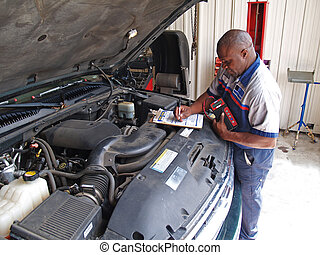 Mechanic Performing a Routine Servi - Auto mechanic...