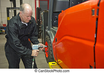 Mechanic tightens wheel nuts on a fork lift with a pneumatic...