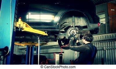 Mechanic polish grind brake system from rust in garage.