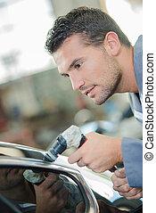 Mechanic polishing a car