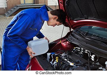 Mechanic Pouring Antifreeze Into Windscreen Water Tank -...