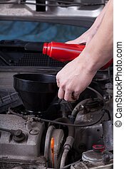 Mechanic pouring oil into car engine