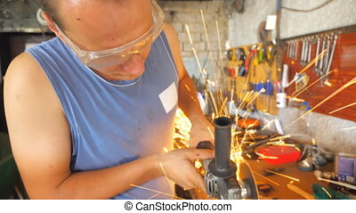 Mechanic processing metal detail with circular saw in garage. Skillful repairer cutting metal using electric grinding wheel. Man wearing protective glasses from sparks during work. Close up.