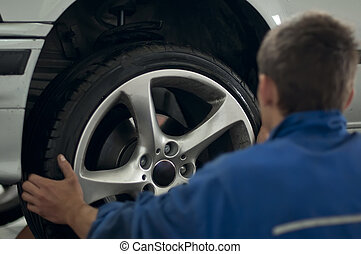 Mechanic put a car tire with alloy wheel