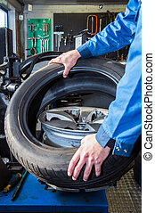 Mechanic putting a tire on a light weight alloy rim
