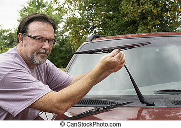 Mechanic Putting New Wiper Blade On - Mechanic putting on a...