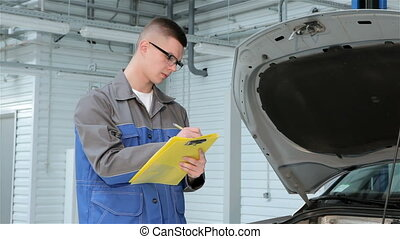 Young mechanic recording car problems to his log book. Blond guy in blue uniform writing in yellow log book. Automotive speacialist in eyeglasses looking at engine compartment of car