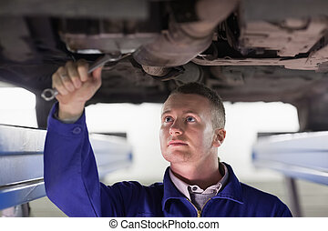 Mechanic repairing a car with a spanner in a garage
