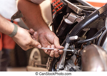 Mechanic Repairing A Motorbike Engine In A Workshop.
