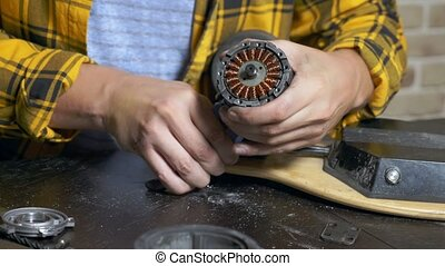 mechanic repairing an electric motor of an electric skate. bearing close up.