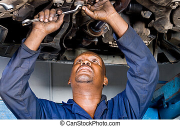mechanic repairing car - a mechanic repairing a car with...