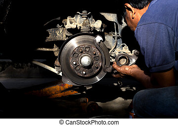 Mechanic repairing car brake disk