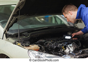 Mechanic repairing car engine - Male mechanic with...