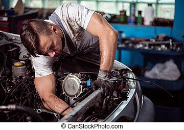 Mechanic repairing car - Picture showing muscular car...