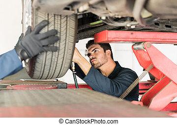 Mechanic Repairing Car Tire In Auto Repair Shop