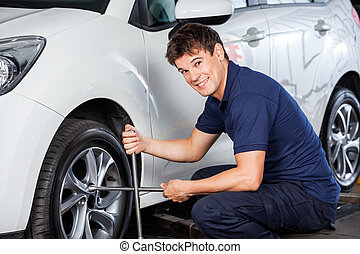 Mechanic Repairing Car Tire With Rim Wrench