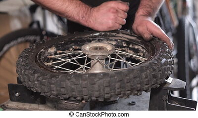 Mechanic repairing damaged motorcycle tire, in repair shop.