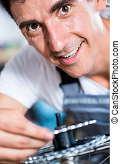 Mechanic repairing gears of bicycle
