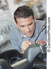 Mechanic repairing handlebars of scooter