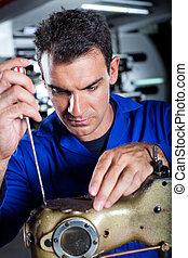 mechanic repairing industrial sewing machine