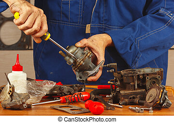 Mechanic repairing parts of automotive engine in the...