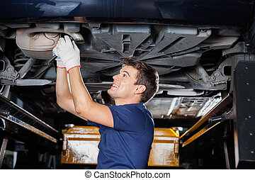 Mechanic Repairing Underneath Car With Wrench