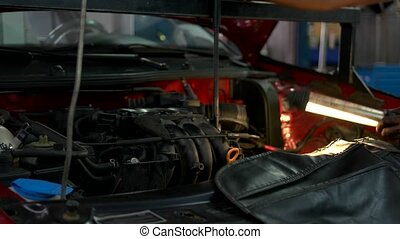 Mechanic repairman lighting car engine. Man examining car ...