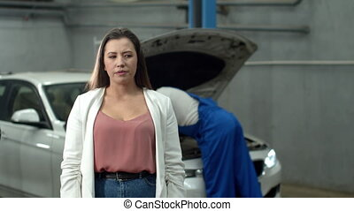 Mechanic repairs a car, dissatisfied woman looks at the camera