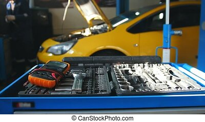 Mechanic repairs a car - in front of metal toolbox, garage...