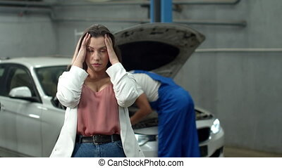 Mechanic repairs a car, indignant woman looks at the camera