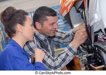 mechanic repairs the carburetor of his motorcycle
