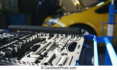 Mechanic repairs yellow car in professional auto service,...