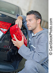 Mechanic replacing a headlight