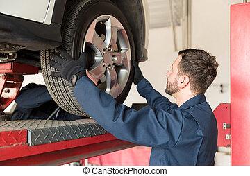 Mechanic Replacing Car Tire At Auto Repair Shop