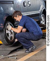 Mechanic Replacing Car Tire At Garage