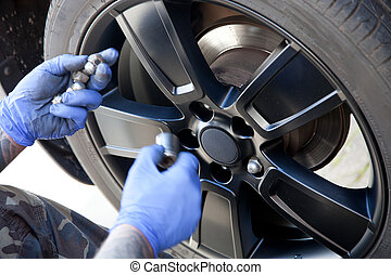 Mechanic replacing the plastic wheel cover after rotating...