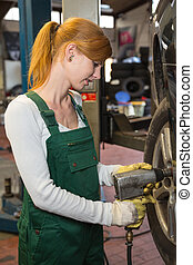 Mechanic replacing the tire or wheel on a car in garage or workshop
