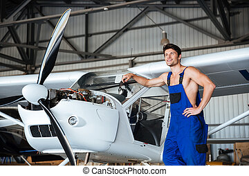 Mechanic resting in front of the plane in a shed