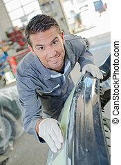 Mechanic sanding down and repairing a bumper