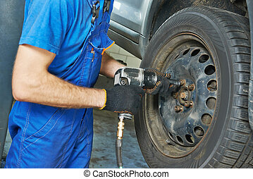 mechanic screwing car wheel by wrench