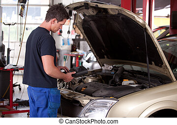 Mechanic Servicing Car - A young mechaing running a ...