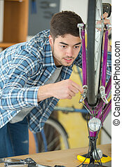 mechanic setting up chain on bicycle in workshop