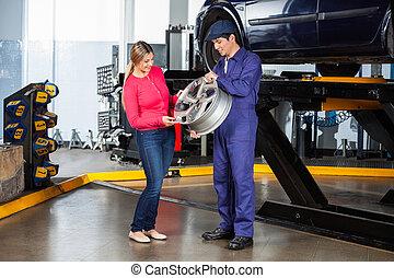 Mechanic Showing Alloy To Customer - Male mechanic showing...