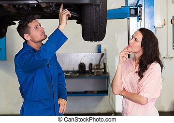 Mechanic showing customer the problem with car at the repair...