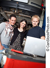 Mechanic Showing Service Order to Customer - A couple with...